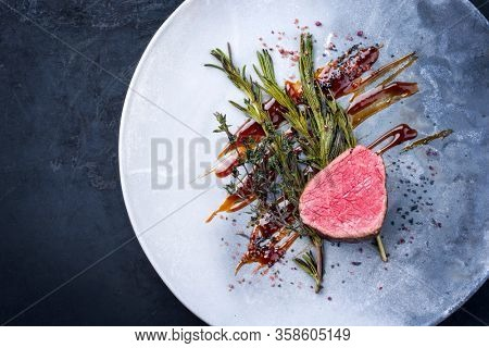 Barbecue dry aged beef fillet medallion steak natural with fried herbs and spice as top view on a modern design plate with copy space left