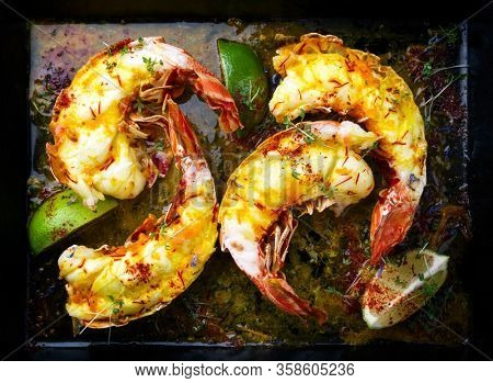 Traditional barbecue spiny lobster tail sliced and offered with saffron lemon sauce as top view on a metal tray