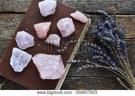 A Top View Image Of Rose Quartz Crystals And Dried Lavender Flowers On An Old Wooden Table.