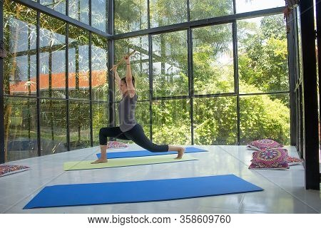 Woman Practicing Yoga In Warrior One Pose In Relaxing Space Virabhadrasana