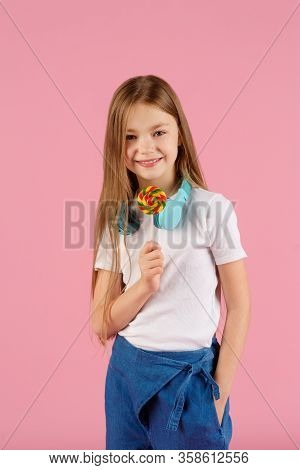 Portrait Of A Surprised Little Girl Holding Heart Shaped Lollipop And Looking At Camera Isolated Ove