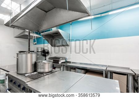 Work Surface And Kitchen Equipment In Professional Kitchen. Cooking With Preparation Tables, Pans, P