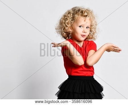 Portrait Of Frolic Curly Hair Blonde Kid Girl In Red T-shirt Holds Holds Hands Up With Open Palms Sa