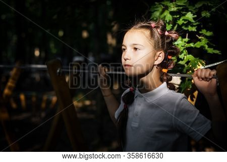 Cute Little Thoughtful Girl With Brown Eyes And Ponytales Holding A Rope At The Evening Playground.
