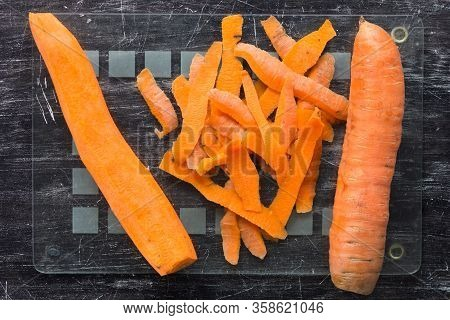 Top View Of Unpeeled Carrot And Peeled Carrot With Peeling On Glass Cutting Board On The Black Backg