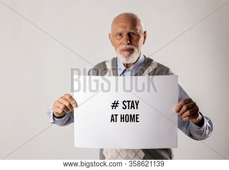 Old Man Is Holding White Paper With Text - Stay At Home. Old Man And Covid-19. Stay At Home And Quar