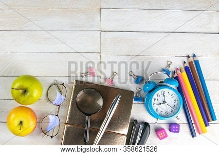 Various Office Stationery, Notepad, Clock, Pencils, Ooh, Glasses, Pen And Two Fresh Apples On A Whit