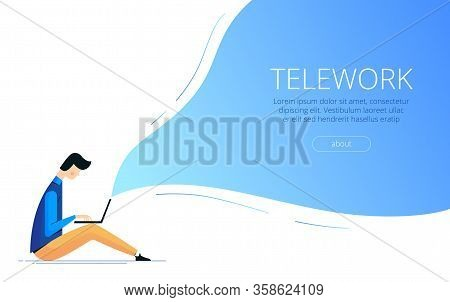 Young Man Freelancer Sits On The Floor With A Laptop And Work Remotely From Home. The Concept Of Tel