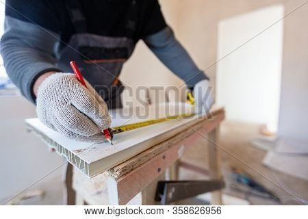 Worker Is Measuring Plastic Detail With Pencil And Tape-line Before Cutting In Apartment That Is Und
