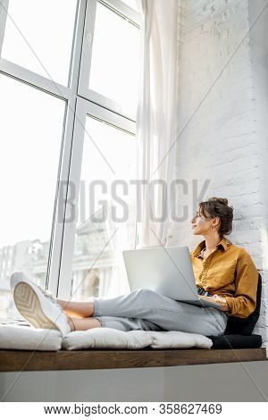 Young Woman Dressed Casually Working On Laptop While Sitting On The Window Sill At Home. Work From H