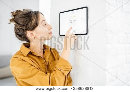Young Woman Controlling Temperature In The Living Room With A Digital Touch Screen Panel. Concept Of