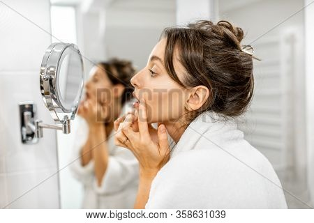 Young Woman In Bathrobe Taking Care Of Her Skin, Looking At The Mirror And Worrying About Wrinkles I