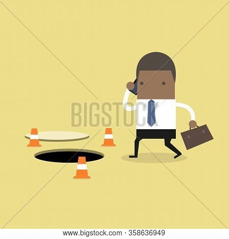 African Businessman Is Talking On The Phone Without Being Careful Of The Hole On The Ground.