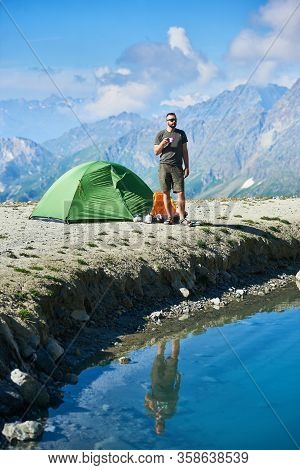 Front View Of Traveler Holding Cup Of Tea While Standing By Tourist Tent, Blue Lake In Mountain Vall