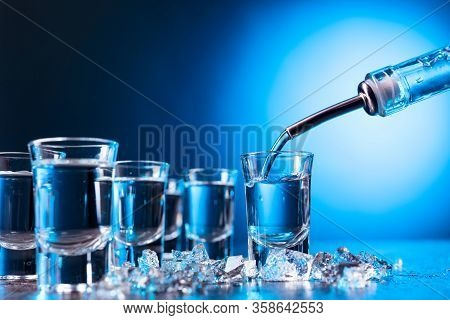 Vodka Poured Into A Glass Lit With Blue Backlight. Copy Space.chilled Vodka With Pieces Of Ice.