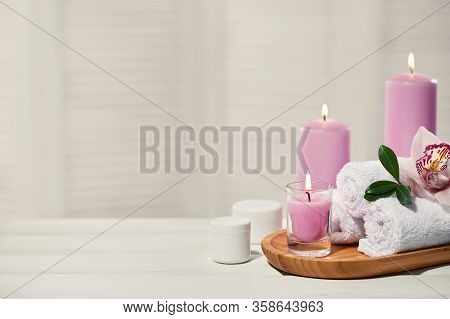 Spa Products With Aromatic Candles, Orchid Flower And Towel On White Wooden Table. Beauty Spa Treatm