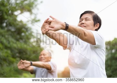 Elderly People Stretching Hands, Arms Before Exercise At Park. Happy Asian Senior Couple Enjoy Worko
