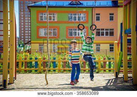 Two Brothers Sibling Boy In Casual Clothes On Playground Climbing Rope And Athletic Rings. Kids Has