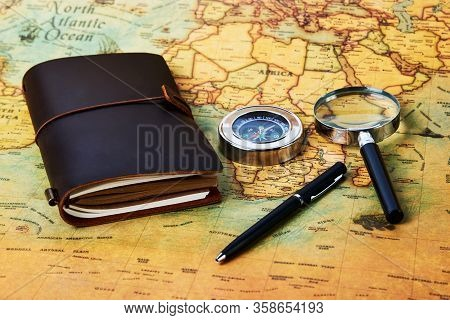 World Map With Business Guide Book, Magnifying Glass And Compass, Close-up