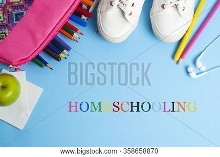 Homeschooling Text Over Blue Background With Colorful Pencils And Sport Shoes. Learn From Home.