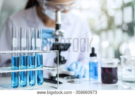 Biochemistry Laboratory Research, Chemist Is Analyzing Sample In Laboratory With Microscope Equipmen