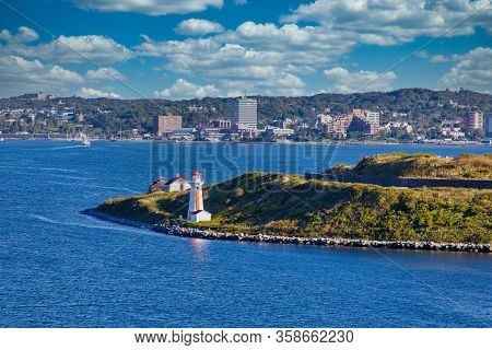 Entrance To Harbor In Halifax, Nova Scotia Marked By An Orange And White Lighthouse On A Point Of Gr