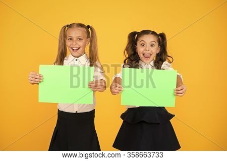 Advertising Idea For School. Happy Girls Holding Paper Sheets For Certain Idea On Yellow Background.