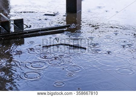 Rain Drops And Water On Concrete With Sky Reflection In Water