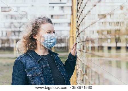 Eastern European Concerned Woman Wearing Medical Mask Outdoors, Standing Next To The Mesh Fence With