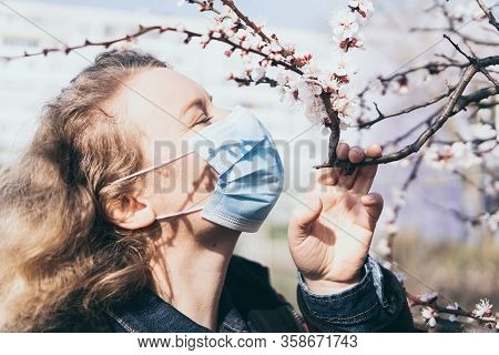 Young Blonde Woman Smells Cherry Tree Blossom Through Medical Mask. Conceptual Image Of Corona Virus