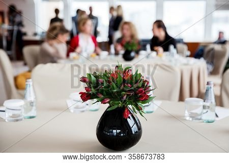 Bouquet Of Beautiful Flowers In Jug Standing On A Large Round Table For Decoration. Business Women A