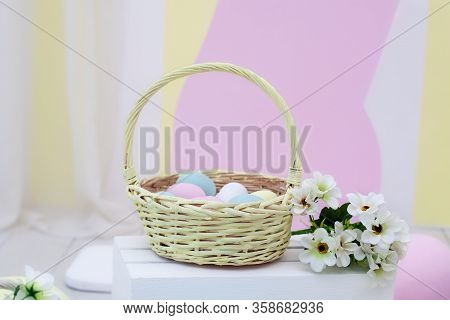 Basket Of Colorful Easter Eggs With Flowers. Wicker Yellow Basket With Easter Eggs On Color Backgrou