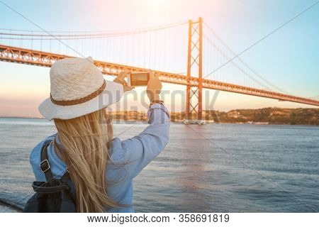 Young traveler woman with smartphone takes pictures in Lisbon of city near the bridge under sunlight in sunny summer day.