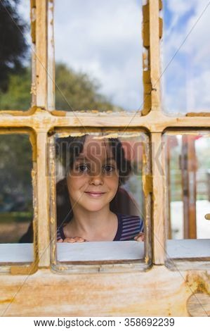 A Curious Boy Looks Out The Window, A Child Looks Out Of The Window Of A Wooden House, Playful Kid,