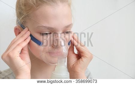Girl With Asthma Inhaler. Girl With Asthma Or Allergy Problems Making Inhalation With Mask On Her Fa