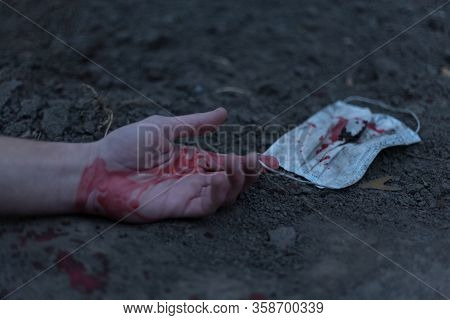 A Medical Bloodied Mask Lies On The Ground With A Bloody Hand Reaching Out. The Concept Of Coronavir