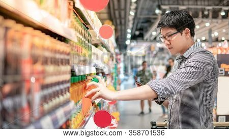 Asian Man Choosing Orange Juice In Supermarket Using Smartphone To Check Shopping List. Male Shopper
