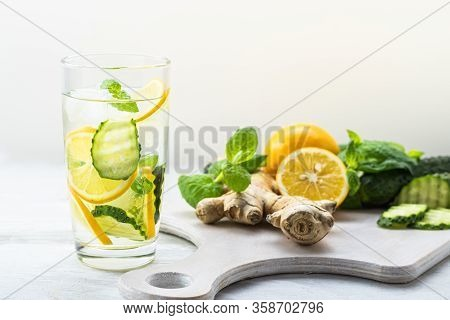 Detox Sassy Water With Lemon, Cucumber, Mint. A Glass Of Clean, Cool And Fresh Drink Stands On A Whi