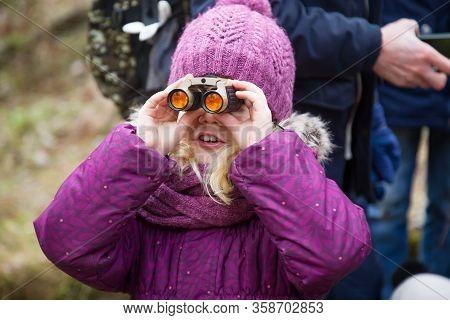 Closeup View Of Small Caucasian Girl Wearing A Purple Hat And Purple Coat Looking Through Binoculars