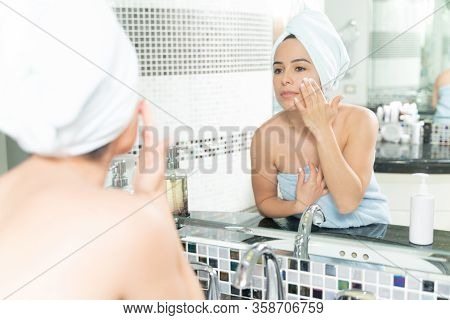 Gorgeous Caucasian Woman Looking At Herself In The Bathroom Mirror And Using Some Facial Cream After