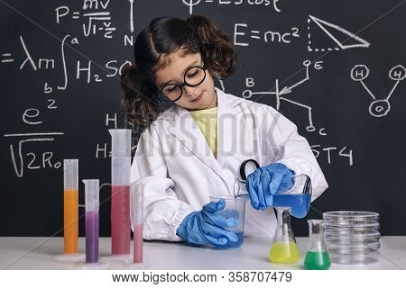 Child Scientist With Glasses And Gloves In Lab Coat Mixing Chemical Liquids In Flasks, On Blackboard
