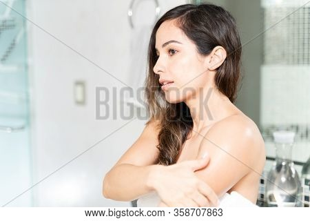 Beautiful Caucasian Woman Wrapped In A Towel And Putting On Some Body Cream In The Bathroom