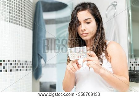 Closeup Of A Caucasian Woman Holding Birth Control Pills While Sitting In The Bathroom