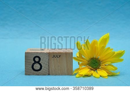 8 July On Wooden Blocks With A Yellow Aster On A Blue Background