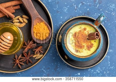 Top View Of Cup Of Golden Turmeric Milk And Plate With Ingredients: Curcuma Powder, Cinnamon, Anise,