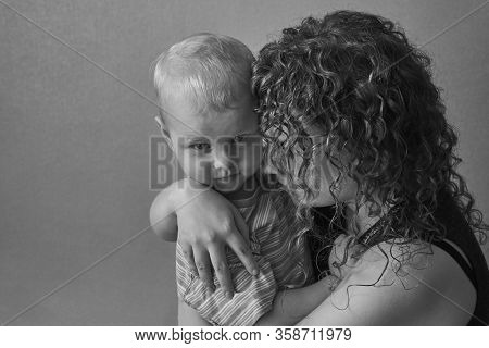 Frightened Mother Hugs Her Little Son, The Theme Of Domestic Violence, Black And White Photo.