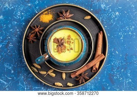 Top View Of Plates With Cup Of Traditional Indian Ayurvedic Golden Turmeric Milk And Ingredients: Cu