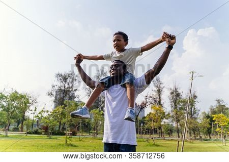 Happy African American Father And Son Piggyback In Outdoor Park. Fatherhood And Family Lifestyle Con