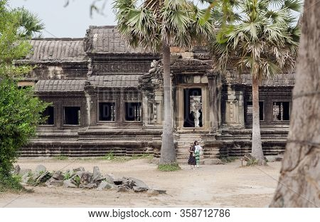 Siem Reap, Cambodia: People Standing On Front Of Angkor Wat Buildind, 12th Century Temple Under Palm