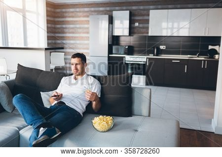 Young Man Watch Tv In His Own Apartment. Sit Alone On Couch And Eat Snacks. Use Remote Control For S